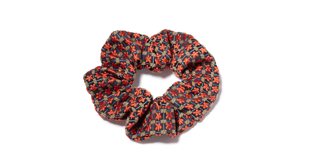 Full view of Crimson Floral Scrunchie. All hail the return of the scrunchie, everyone's favorite fabric-covered elastic hair tie! Our version amps up the luxury factor in a crimson floral patterned silk jacquard.