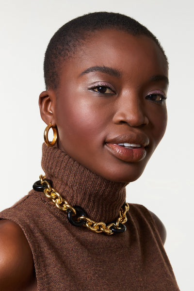 Thumbnail of model wearing the Zodiac Collar. Keep it classic but make it bold -- you'll be good as gold in our chunky collar necklace with oversized black acrylic links.