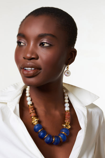 Thumbnail of model wearing the Bombay Blue Necklace. Pow! We love combining pearls with pops of color for a bright take on the classic. This gold-plated necklace highlights oversized cobalt blue glass beads strung with bauxite and freshwater pearls.