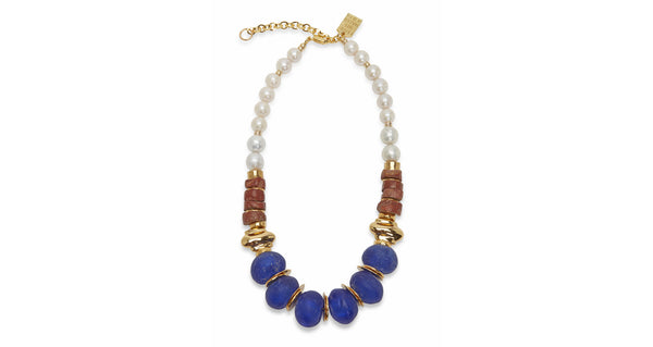 Full view of Bombay Blue Necklace. Pow! We love combining pearls with pops of color for a bright take on the classic. This gold-plated necklace highlights oversized cobalt blue glass beads strung with bauxite and freshwater pearls.