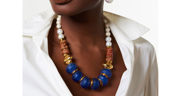 Model wearing the Bombay Blue Necklace. Pow! We love combining pearls with pops of color for a bright take on the classic. This gold-plated necklace highlights oversized cobalt blue glass beads strung with bauxite and freshwater pearls.