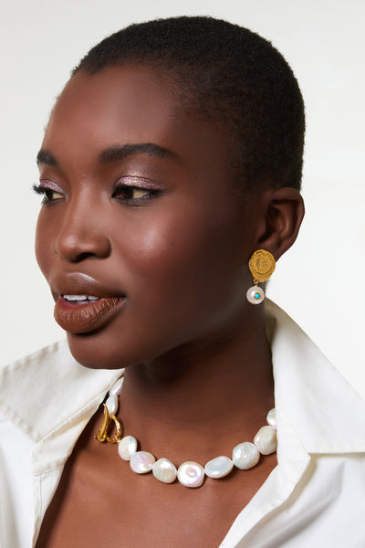 "Thumbnail of model wearing the Goa Pearl Collar. The world is your oyster in this elegant update on the most timeless of accessories, the pearl necklace. Featuring freshwater coin pearls with gold-plated ""claw"" toggle closure. A wardrobe classic for you, your mother, or your best friend."