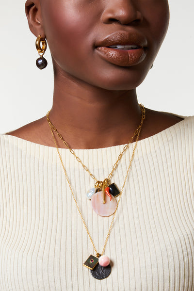 Thumbnail of model wearing the Indira Charm Necklace. Assert your style independence with a gold vermeil chain necklace that projects both beauty and strength. This longer charm necklace features a cast, oxidized antique coin pendant, conch shell drop, and black mother-of-pearl rectangle with faceted garnet detail.