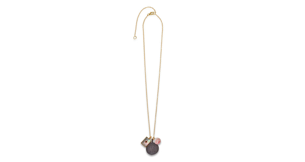 Full view of Indira Charm Necklace. Assert your style independence with a gold vermeil chain necklace that projects both beauty and strength. This longer charm necklace features a cast, oxidized antique coin pendant, conch shell drop, and black mother-of-pearl rectangle with faceted garnet detail.