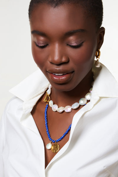Thumbnail of model wearing the Indigo Charm Necklace. Easy to wear, lovely to layer. Our blue striped African glass bead necklace lends just the right pop of color to any outfit and features a gold-plated cast antique coin pendant, freshwater pearl charm, and adjustable burgundy cord closure.