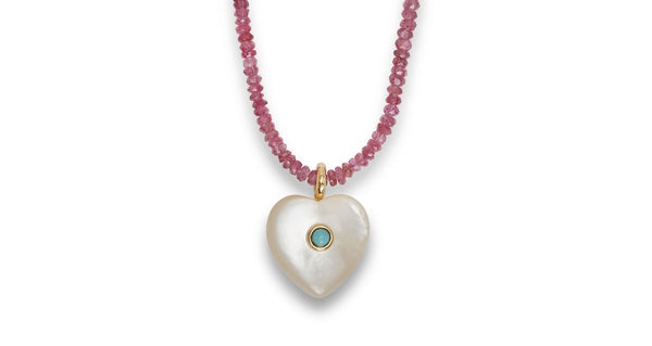 Close-up view of Simple Heart Necklace In Raspberry. The simple fact is we'll be wearing this pretty necklace all the time. The sweet mother-of-pearl heart charm is inlaid with a turquoise cabochon and surrounded by faceted pink spinel beads. The black cord closure is adjustable so you can layer it with your other necklaces (since you won't want to take this one off!).