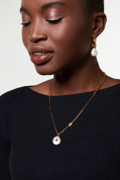 Thumbnail of model wearing the Red Eye Pearl Necklace. Bring good vibrations to your wardrobe in this simple, elegant gold vermeil chain necklace with freshwater coin pearl pendant and faceted pink tourmaline detail. We truly want to wear this one everyday.