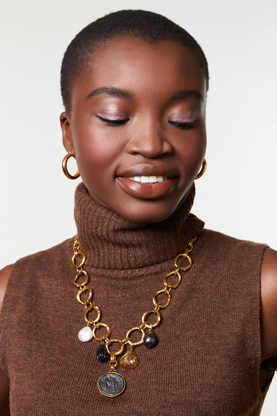 Thumbnail of model wearing Byzantine Charm Necklace. Make a statement in this warm-toned round link chain necklace with heirloom-worthy details. With a cascade of hanging pearls, black agate drop, and carved quartz charm set to showcase a cast, oxidized antique coin pendant.