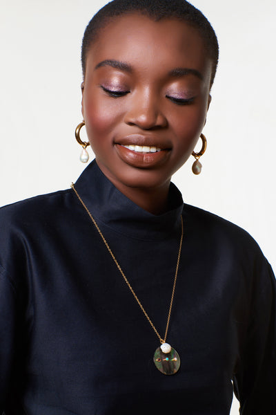 Thumbnail of model wearing the Equator Pendant Necklace. The classic pearl goes uniquely contemporary in this sleek pendant necklace. A thin gold vermeil chain holds a freshwater pearl charm and iridescent black mother-of-pearl disc set with garnet, turquoise, and pearl cabochons.