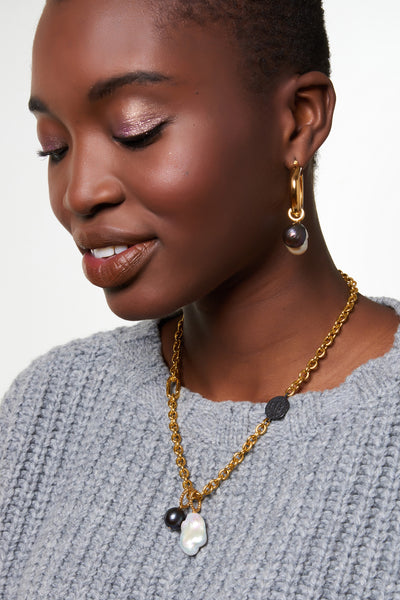 Thumbnail of model wearing Ancient Coin Necklace. We're mad for the subtle asymmetry of the gold-plated chain necklace with cast, oxidized antique coin detail set off to the side. Finished with white and peacock-colored pearl charms, this piece has the makings of an understated heirloom.