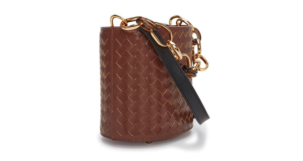 Side view of Florent Bucket Bag In Woven Leather. Our essential bucket bag has been given a luxe upgrade in brown woven leather, with acrylic and gold-plated large-link top handle. Equestrian vibes meet practical urban details such as a detachable black leather cross-body strap and microsuede interior drawstring closure.