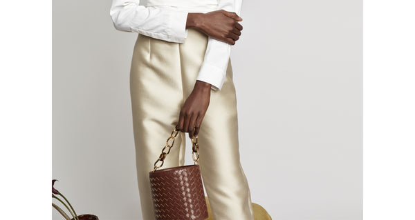 Model holding the Florent Bucket Bag In Woven Leather. Our essential bucket bag has been given a luxe upgrade in brown woven leather, with acrylic and gold-plated large-link top handle. Equestrian vibes meet practical urban details such as a detachable black leather cross-body strap and microsuede interior drawstring closure.