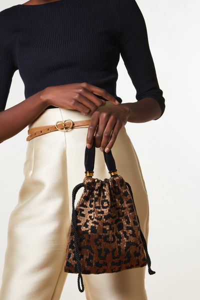 Thumbnail of model holding the Gala Wristlet In Cheetah. Show off your animal instincts with our party-ready drawstring purse in a bold leopard-print pattern. With hand-sewn brown and black bugle beads and lush black velvet top handle.