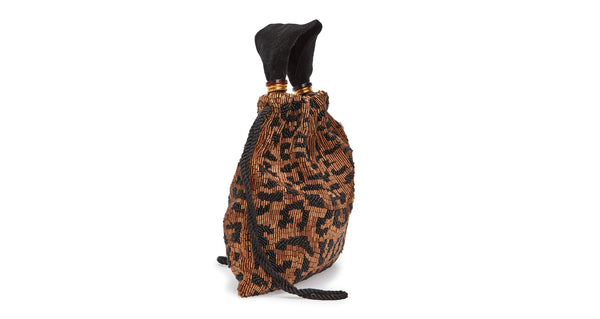 Side view of Gala Wristlet In Cheetah. Show off your animal instincts with our party-ready drawstring purse in a bold leopard-print pattern. With hand-sewn brown and black bugle beads and lush black velvet top handle.