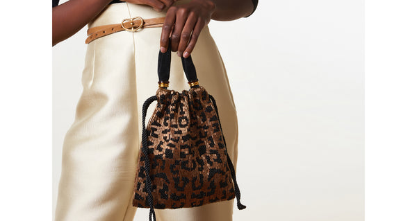 Model holding the Gala Wristlet In Cheetah. Show off your animal instincts with our party-ready drawstring purse in a bold leopard-print pattern. With hand-sewn brown and black bugle beads and lush black velvet top handle.