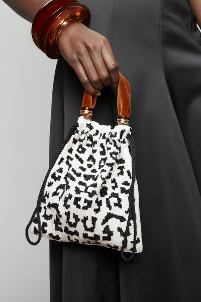 Thumbnail of model holding Gala Wristlet In Black & White Spot. Show off your animal instincts with our party-ready drawstring purse in a boldly graphic leopard-print pattern. With hand-sewn black and white bugle beads and lush burnt orange velvet top handle.
