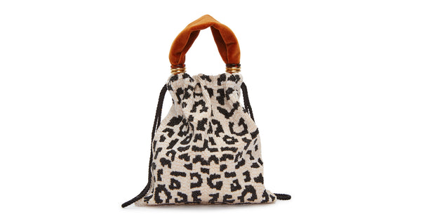 Full view of Gala Wristlet In Black & White Spot. Show off your animal instincts with our party-ready drawstring purse in a boldly graphic leopard-print pattern. With hand-sewn black and white bugle beads and lush burnt orange velvet top handle.