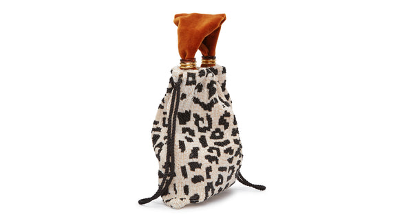 Side view of Gala Wristlet In Black & White Spot. Show off your animal instincts with our party-ready drawstring purse in a boldly graphic leopard-print pattern. With hand-sewn black and white bugle beads and lush burnt orange velvet top handle.