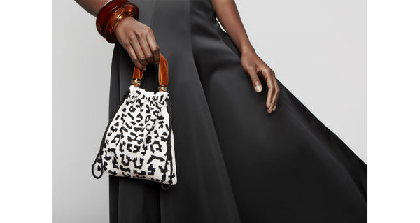 Model holding Gala Wristlet In Black & White Spot. Show off your animal instincts with our party-ready drawstring purse in a boldly graphic leopard-print pattern. With hand-sewn black and white bugle beads and lush burnt orange velvet top handle.