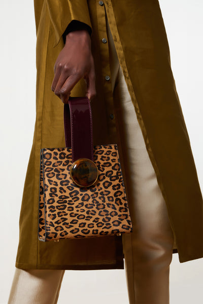 Thumbnail of model holding the Pronto Purse In Bold Leopard. The wildcat's out of the bag-- our newest Pronto structured mini purse is a feat of polished perfection, in leopard print calf hair and brown leather. With patent leather top handle, round acrylic ornament and detachable black leather cross-body strap.
