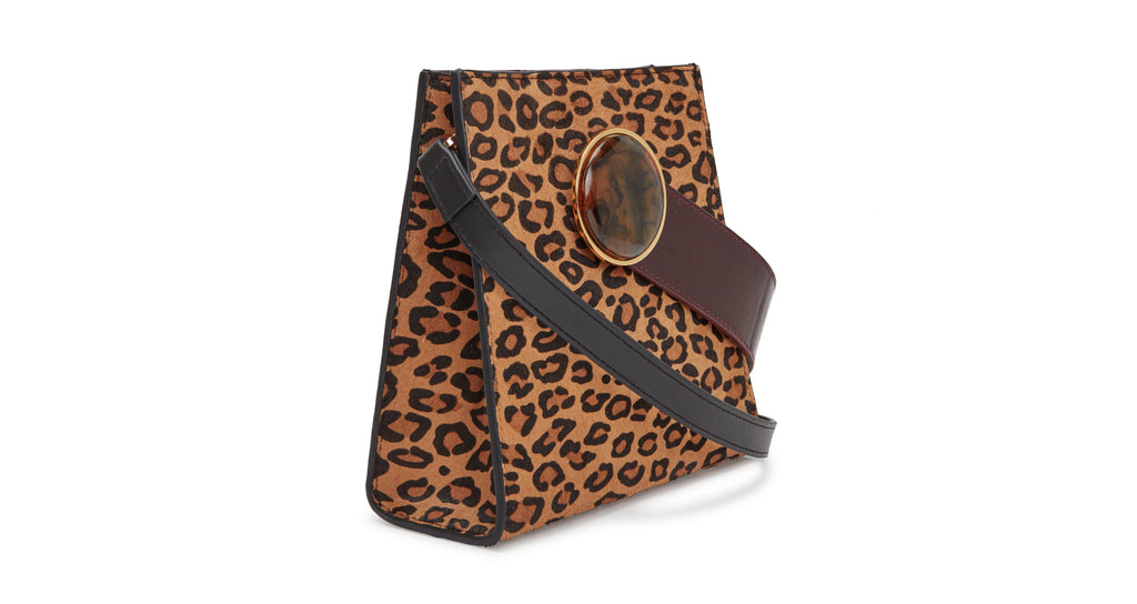 Full side view of Pronto Purse In Bold Leopard. The wildcat's out of the bag-- our newest Pronto structured mini purse is a feat of polished perfection, in leopard print calf hair and brown leather. With patent leather top handle, round acrylic ornament and detachable black leather cross-body strap.