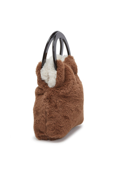 Thumbnail side view of Alpine Bag In Off-White & Brown, brown side showing. Snuggle up to our reversible(!) off-white and brown faux-fur mini bag, with black acrylic round handles. It's a great way to add a dose of cozy texture to an outfit and a surefire conversation starter.