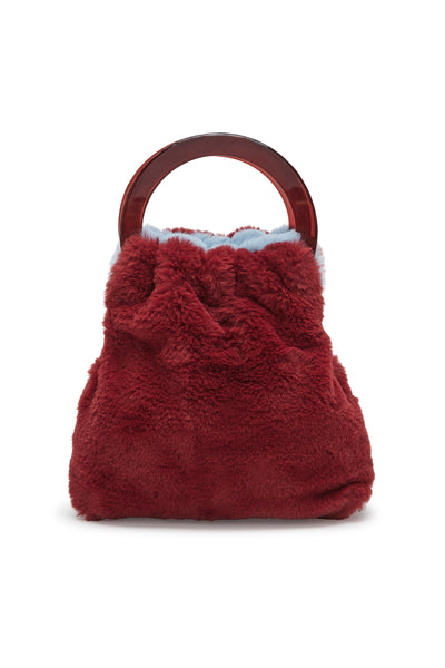 Thumbnail of Alpine Bag In Sky & Burgundy, burgundy side showing. Snuggle up to our reversible(!) sky-blue and burgundy faux-fur mini bag, with tortoise-colored acrylic round handles. It's a great way to add a dose of cozy texture to an outfit and a surefire conversation starter.