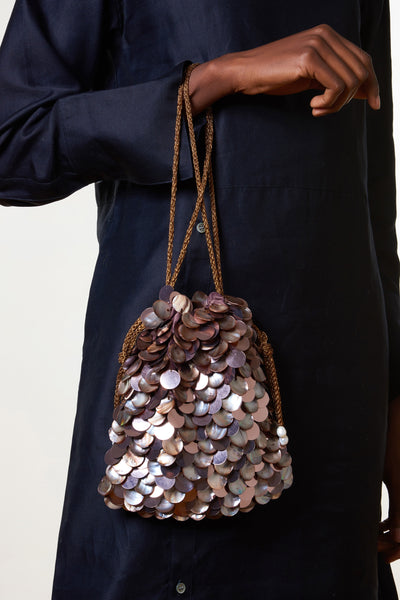 Thumbnail of model holding the Gala Wristlet In Sundown. Calling all mermaids. This gorgeous drawstring purse is all set to sparkle and shine at your next night out. With hand-sewn dark gray shells and sequins, and bronze twist cord wristlet.
