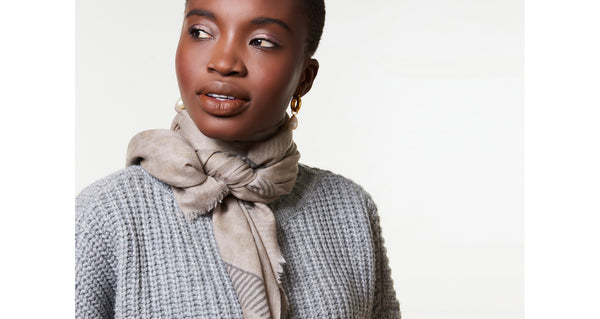 Model wearing The Heritage Scarf in Leopard. Bundle up in our most versatile fall accessory, the long rectangular wool blend scarf with leopard print, two-tone crosshatch border print, and fringed edges. If you're shy about wearing animal prints, this will be your gateway piece.
