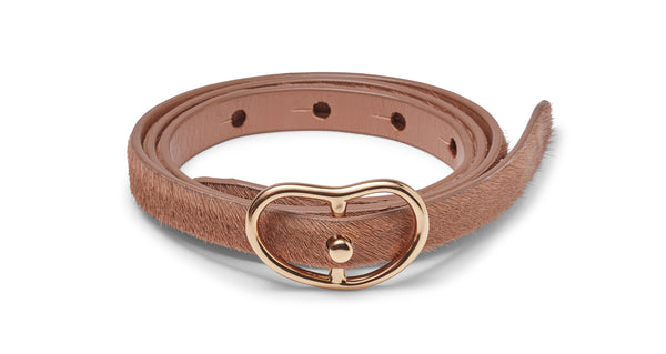 Full view of Skinny Georgia Belt In Tan Calf Hair. Here's a subtly textured take on our classic thin leather belt. In tan calf hair with gold-plated buckle.