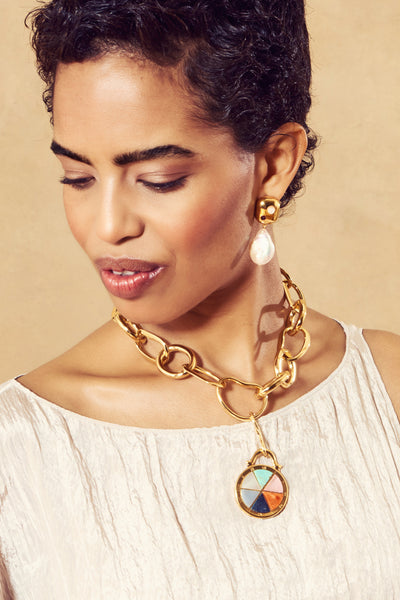 Thumbnail of model in the Porto Necklace In Compass. With its oversized gold links and detac...