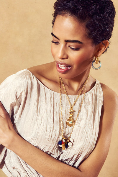 Thumbnail of model in the Heritage Charm Necklace. Meet your newest heirloom accessory— the ...