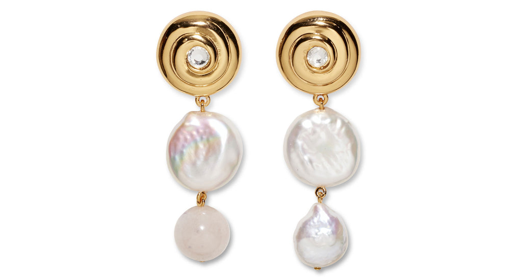 Full view of LFJ x The Wing Exclusive Earrings. We've collaborated with The Wing to create a web-exclusive, limited-edition pair of earrings inspired by the unique female friendships and dreamy color palette found on HBO's Big Little Lies.  These earrings feature gold-plated 'swirl' tops with crystal accents, and asymmetric drops of freshwater coin pearls and rose quartz.
