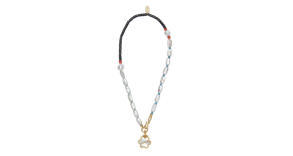 Full view of Rip Tide Necklace. How to make a simple summer t-shirt look phenomenal? Layer up your accessories! Everything is elevated when paired with the Rip Tide, an asymmetric single-strand beaded necklace with assorted glass beads, pearls, and mother-of-pearl bisected daisy pendant.