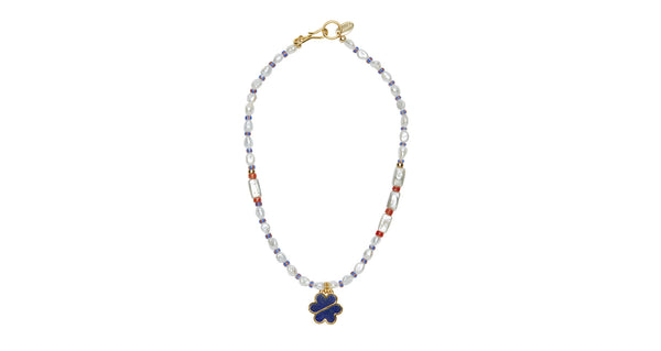 Full view of Ocean Drive Necklace. How to make a simple summer t-shirt look phenomenal? Layer up your accessories with our elevated take on the classic beaded friendship necklace from your camp days. The single-strand beaded necklace with African glass, pearls, and lapis bisected daisy pendant is the perfect blend of sophistication and nostalgia.