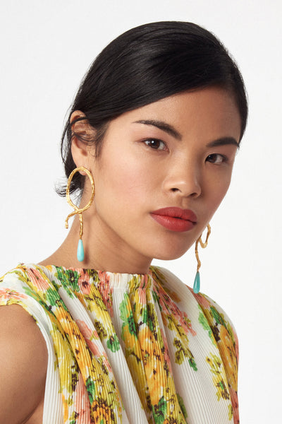 Thumbnail of model wearing Cursive Earrings. Equal parts cool and romantic, our textured, abstract swirl earrings are inspired by the graceful swoops of cursive handwriting. Punctuated by hanging teal-colored pearl drops.
