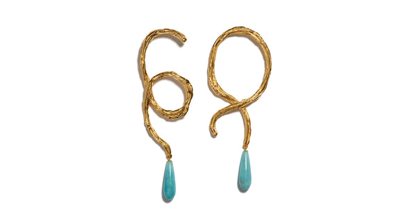 Full view of Cursive Earrings. Equal parts cool and romantic, our textured, abstract swirl earrings are inspired by the graceful swoops of cursive handwriting. Punctuated by hanging teal-colored pearl drops.