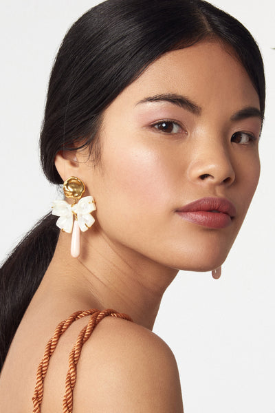 "Thumbnail of model wearing Charlotte Earrings. Feminine and unique, these gold ""coin"" earrings feel just right paired with a tulle dress -- or thrown on to sweeten up a chambray shirt. With hanging mother-of-pearl carved bows and light pink conch drops."