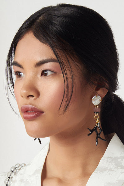"Thumbnail of model wearing Florentine Earrings. Organic shapes and a sophisticated color scheme mean these earrings can easily transition from the office to the beach. Gold-plated hardware with black ""branch coral,"" pink quartz beads, and pearl tops."
