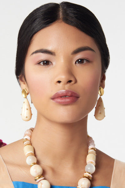 Thumbnail of model wearing Prism Earrings In Cream. The classic drop earrings so chic, you will wear them forever -- now in a smooth cream acrylic with gold-plated stud details.