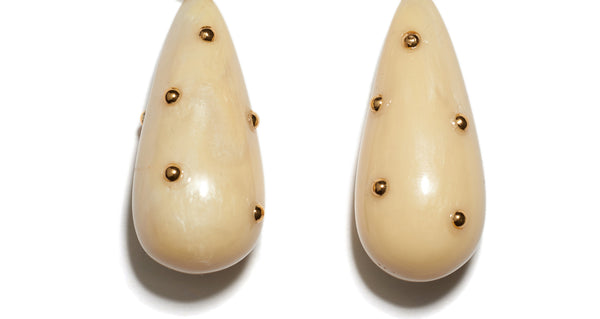 Bottom detail of Prism Earrings In Cream. The classic drop earrings so chic, you will wear them forever -- now in a smooth cream acrylic with gold-plated stud details.