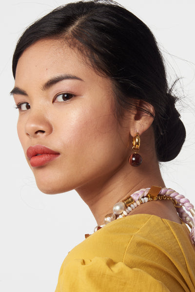 Thumbnail of model wearing Tiger Eye Hoops. We love the warm and timeless vibe of these gold-plated hoop earrings with tiger eye bead drops. Prediction: these will become your favorite everyday go-to pair.
