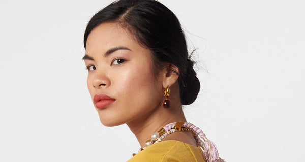 Model wearing Tiger Eye Hoops. We love the warm and timeless vibe of these gold-plated hoop earrings with tiger eye bead drops. Prediction: these will become your favorite everyday go-to pair.