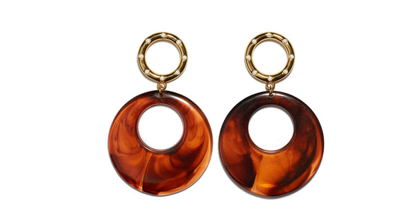 Full view of La Fonda Earrings. We love how these charmingly retro earrings fit seamlessly with contemporary styles. Gold and enamel rings with lightweight butterscotch-colored acrylic hoops.