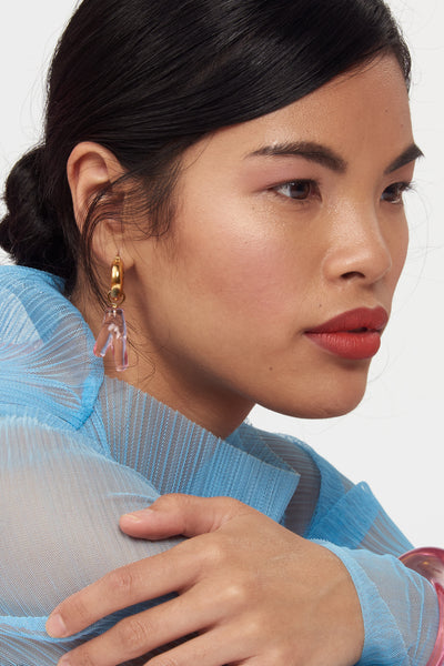 Thumbnail of model wearing Pink Reef Earrings. Sleek, modern earrings with just the right amount of charm. The transparent acrylic coral adds an approachable amount of statement to our classic, gold plated hoops.