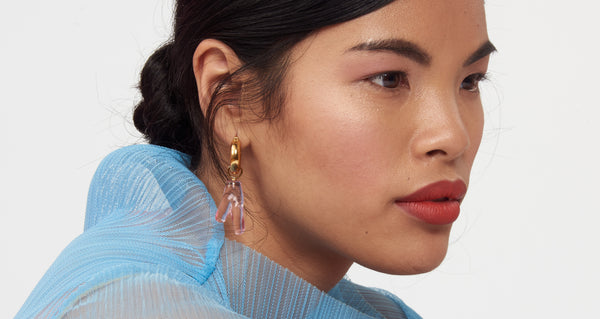 Model wearing Pink Reef Earrings. Sleek, modern earrings with just the right amount of charm. The transparent acrylic coral adds an approachable amount of statement to our classic, gold plated hoops.