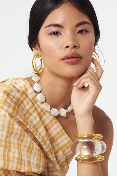 Thumbnail of model wearing Rome Hoops In Lemon. Elevate your everyday earrings game in our lightweight dyed resin hoops, now in lemon. A modern take on pastels; we love how they pair with the transparent Arc Cuff.