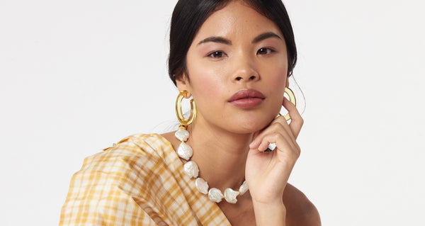 Model wearing Rome Hoops In Lemon. Elevate your everyday earrings game in our lightweight dyed resin hoops, now in lemon. A modern take on pastels; we love how they pair with the transparent Arc Cuff.