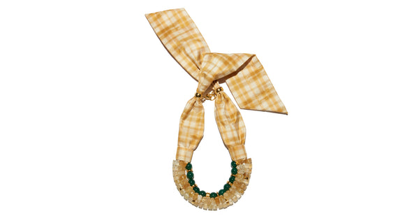 Full view of Picnic Necklace. The perfect blend of substance and whimsy, you'll stun in the citrine, green agate, and gold bead triple-strand statement necklace. Seal the deal with the yellow and white plaid silk taffeta tie.