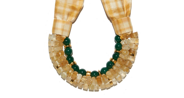 Bottom detail of Picnic Necklace. The perfect blend of substance and whimsy, you'll stun in the citrine, green agate, and gold bead triple-strand statement necklace. Seal the deal with the yellow and white plaid silk taffeta tie.
